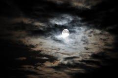 Volle maan en witte wolken op zwarte nachthemel stock foto