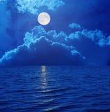 Volle maan in hemel met wolken over overzees Stock Foto