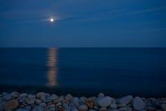Volle maan met bezinning over overzees Stock Foto