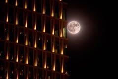 Volle maan op de achtergrond van een wolkenkrabber Stock Fotografie