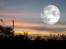 volle maan op donkere de wolk en het silhouet elektrische macht van de zonsonderganghemel Stock Fotografie
