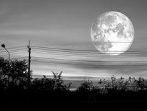 volle maan op donkere de wolk en het silhouet elektrische macht van de zonsonderganghemel Stock Afbeelding