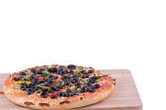 Volle Pizza auf einer Seitenansicht des hackenden Brettes Stockfoto