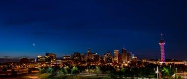 Volle Skyline von Denver Colorado nachts mit einem Mond Stockfoto
