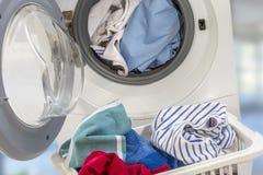 Volle Waschmaschine und Kleidung im Korb auf weißem Hintergrund Stockfotografie
