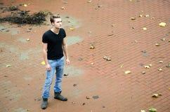 Volle Zahl schoss vom jungen Mann allein im Großen leeren Raum stockbild