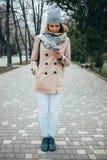 Volledig lengte verticaal portret van jonge vrouw die beige trenc dragen stock fotografie