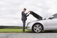 Volledig lengte zijaanzicht die van jonge zakenman opgesplitste autokap openen bij platteland Royalty-vrije Stock Foto's