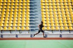 Volledig lengte zijaanzicht van een sportman die op renbaan lopen Royalty-vrije Stock Foto's