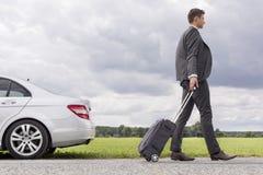 Volledig lengte zijaanzicht van jonge zakenman met bagage die opgesplitste auto verlaten bij platteland Royalty-vrije Stock Afbeeldingen