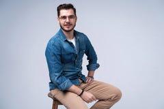 Volledig lengteportret van een aantrekkelijke jonge mens in de zitting van het jeansoverhemd op de stoel over grijze achtergrond royalty-vrije stock fotografie