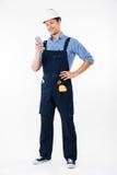 Volledig lengteportret van een bouwer die en telefoon bevinden zich met behulp van Royalty-vrije Stock Foto