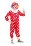 Volledig lengteportret van een glimlachende gelukkige clown in rood kostuum giv Royalty-vrije Stock Afbeelding