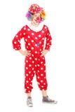 Volledig lengteportret van een glimlachende gelukkige clown in rood kostuum pos stock afbeeldingen