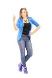Volledig lengteportret van een glimlachende toevallige vrouw die een duim opgeven Stock Foto