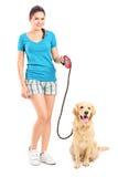 Volledig lengteportret van een jong meisje die een hond lopen stock foto