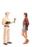Volledig lengteportret van een leveringsjongen die een bos van bloem houden Stock Foto