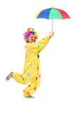 Volledig lengteportret van een mannelijke clown met paraplu Royalty-vrije Stock Afbeeldingen