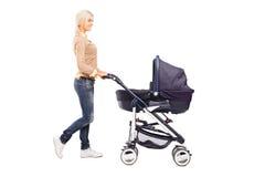 Volledig lengteportret van een moeder die een babywandelwagen duwen Stock Afbeeldingen