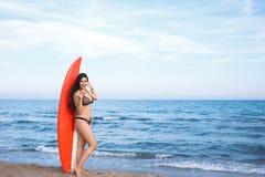 Volledig lengteportret van een overweldigend wijfje zich met surfplank tegen blauwe overzees bevinden en kalme hemelachtergrond d Stock Fotografie