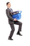 Volledig lengteportret van een professionele mens die zware omslag dragen Stock Foto's