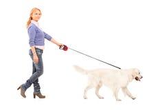 Volledig lengteportret van een vrouw die een hond loopt Stock Afbeeldingen