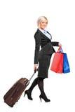 Volledig lengteportret van een vrouwen dragende koffer Stock Foto's