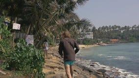 Volledig lengteportret van erachter van aantrekkelijke surfer die in zand door water op Sri Lanka lopen stock footage