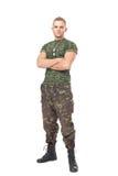 Volledig lengteportret van ernstige legermilitair met zijn wapenskruis stock foto's