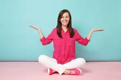 Volledig lengteportret van glimlachende jonge vrouw die in die roze overhemdsblouse, witte broek op vloer zitten op helder roze w royalty-vrije stock afbeelding