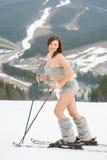 Volledig lengteportret van glimlachende sexy vrouwenskiër die zich op de sneeuwhelling van de berg bevinden stock foto