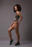 Volledig lengteportret van grappige speelse verbaasde jonge zwarte Afrikaanse vrouw in swimwear en tennisschoenen over grijze ach royalty-vrije stock foto