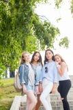 Volledig lengteportret van het charmeren van jonge studentenmeisjes in het Park in de zomer De vrouwen dragen pastelkleur kleurde stock foto