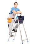 Volledig lengteportret van het handige mens stellen op een ladder Royalty-vrije Stock Afbeelding