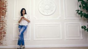 Volledig lengteportret van jonge vrouw, meisje, brunette, in witte overhemd en jeans, die zich op achtergrond van witte muur bevi stock video