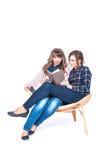 Volledig lengteportret van twee die mooie weman studenten situeren die boeken houden die op een witte achtergrond worden geïsolee Stock Fotografie