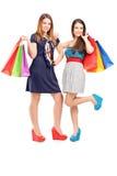 Volledig lengteportret van twee jonge wijfjes die het winkelen zakken houden Stock Afbeelding