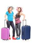Volledig lengteportret van twee tieners met koffers   Stock Foto's