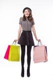 Volledig lengteschot van aantrekkelijke jonge die de kleurendocument van de vrouwenholding het winkelen zakken op wit worden geïs Stock Afbeelding