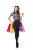 Volledig lengteschot van aantrekkelijke jonge die de kleurendocument van de vrouwenholding het winkelen zakken op wit worden geïs Stock Foto's