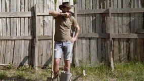 Volledig lichaamsportret van gebaarde mensenlandbouwer met schop die pret in een landbouwbedrijf op houten dackground hebben Ecol stock video