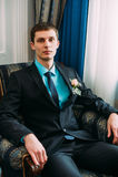 Volledig lichaamsportret van jonge modieuze zakenman in band en vest met handen op taille Stock Fotografie