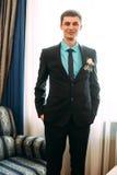 Volledig lichaamsportret van jonge modieuze zakenman in band en vest met handen op taille Stock Afbeeldingen