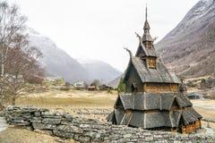 Volledig - mening van ingewikkelde die staafkerk in Noorwegen door rotsmuur wordt omringd royalty-vrije stock afbeeldingen