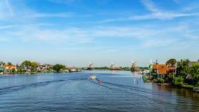 Volledig - operationele historische Nederlandse Windmolens en huizen langs de Zaan-Rivier Stock Foto's