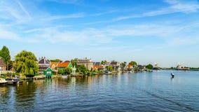 Volledig - operationele historische Nederlandse Windmolens en huizen langs de Zaan-Rivier Stock Afbeeldingen