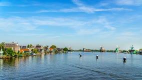 Volledig - operationele historische Nederlandse Windmolens en huizen langs de Zaan-Rivier Stock Foto