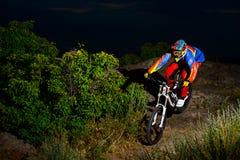 Volledig Uitgeruste Professionele bergaf Fietser die de Fiets berijden op de Nacht Rocky Trail royalty-vrije stock foto's
