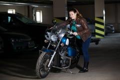 Volledig-voorgestelde vrouw die op fiets in donkere garage, concept krijgt zwanger met motorfiets stock foto's