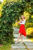 Volledige aantrekkelijke gelukkige het blondevrouw van het lengteportret in het modieuze rode witte kleding stellen dichtbij bloe royalty-vrije stock afbeeldingen